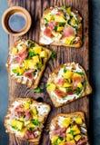 Grzanki z kremowym serem, baleronu jamon serrano i mango, słuzyć na drewnianej desce z czerwonym winem, szarości łupkowy tło, wie Fotografia Royalty Free