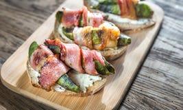 Grzanki z kremowym serem i avocado zawijającymi w bekonie Fotografia Stock