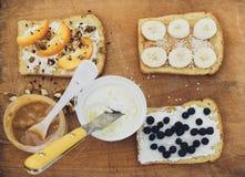 Grzanki z masłem orzechowym, serem i owoc na drewnianym tle, Fotografia Stock