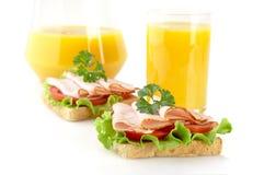 Grzanki z zimnymi cięciami dla śniadania z sokiem pomarańczowym na bielu Zdjęcie Royalty Free