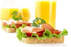 Grzanki z zimnymi cięciami dla pory lunchu z sokiem pomarańczowym na bielu Obraz Royalty Free