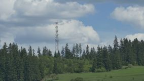 GSM Antenna on Mountain. Timelapse with passwing clouds over a mountain and fir forest GSM antenna station stock video footage