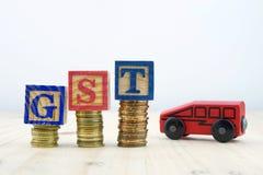GST-begrepp med träkvarter som staplas på av mynt med leksakbilen Arkivbilder