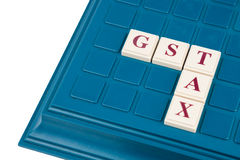 GST-BELASTINGSconcept met kruiswoordraadsel op een raadsspel Stock Afbeeldingen