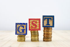 GST concept with wooden blocks on stacked of coins Royalty Free Stock Photography