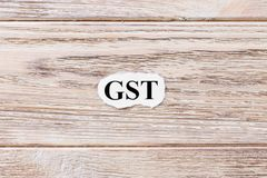 GST della parola su carta Concetto Parole di GST su un fondo di legno Fotografia Stock