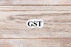 GST des Wortes auf Papier Konzept Wörter von GST auf einem hölzernen Hintergrund Stockfoto