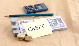 GST, or Goods and Services Tax, Concept. GST or goods and services tax concept, highlighted with a bundle of  Indian rupees and stacks of coins and handwritten Stock Photos