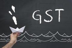 GST pojęcie Męska ręki mienia papieru łódź na blackboard z inskrypcją GST Fotografia Royalty Free