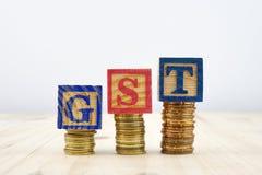 GST pojęcie z drewnianymi blokami dalej brogującymi monety Fotografia Royalty Free