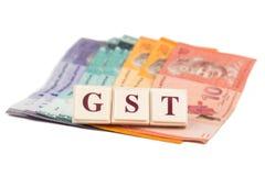 GST-STEUER-Konzept mit Alphabet vom Brettspiel und der Währung Stockbild