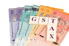 GST-STEUER-Konzept mit Alphabet vom Brettspiel und der Währung Stockbilder