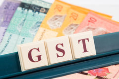 GST TAX concept with  alphabet from board game and currency Royalty Free Stock Photo