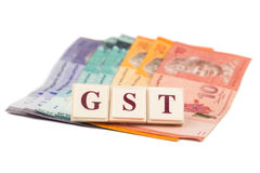GST TAX concept with  alphabet from board game and currency Stock Image