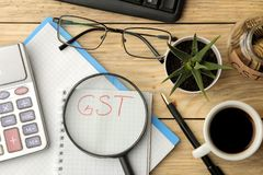 GST word in notebook under magnifying glass and calculator, pen and coffee on brown wooden background. view from above stock images