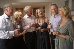 Gäste, die Champagne am Abendessen genießen Stockfotografie