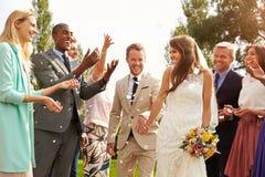Gäste, die Konfettis über Braut und Bräutigam At Wedding werfen Lizenzfreie Stockbilder