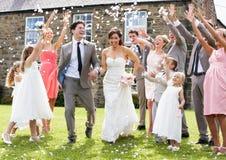 Gäster som kastar konfettier över brud och brudgum Arkivfoton