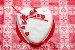 Gâteau blanc de forme de coeur avec le ruban rouge de coeurs Images stock