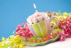 Gâteau d'anniversaire dans la tasse de thé avec la bougie de Lit Photo stock