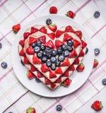 Gâteau fait maison avec des fraises et des myrtilles pour la Saint-Valentin en forme de coeur d'un plat blanc sur une nappe rayée Photos stock