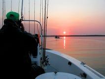 Guía de la pesca en el lago en la salida del sol fotografía de archivo libre de regalías
