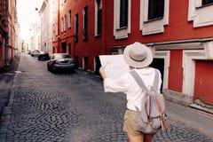 Guía del viaje Viajero femenino joven con la mochila y con el mapa en la calle concepto del recorrido Imagen de archivo