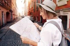 Guía del viaje Viajero femenino joven con la mochila y con el mapa en la calle concepto del recorrido Fotografía de archivo libre de regalías