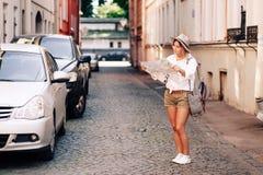 Guía del viaje Viajero femenino joven con la mochila y con el mapa en la calle concepto del recorrido Imagenes de archivo
