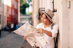 Guía del viaje Viajero femenino joven con la mochila y con el mapa en la calle concepto del recorrido Fotografía de archivo