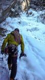 Guía masculina de la montaña que se acerca a una cascada congelada escarpada después de una excursión que sube del hielo Fotos de archivo libres de regalías