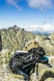 Guía turística, un casco y una mochila con los picos en el fondo Fotos de archivo libres de regalías