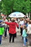 Guía turístico femenino que dice y que muestra a turistas algo en Peter y Paul Fortress en St Petersburg, Rusia Imágenes de archivo libres de regalías