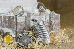 GU10 LED bulbs on straw in front of old delivery wooden box with Royalty Free Stock Images