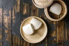 Gua bao buns. Empty gua bao steamed buns in ceramic plate and opened bamboo steamer over dark wooden plank background. Flat lay, space. Asian fast food stock photo