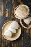 Gua bao buns. Empty gua bao steamed buns in ceramic plate and opened bamboo steamer over dark wooden plank background. Flat lay, space. Asian fast food stock images