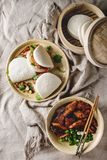 Gua bao buns with pork. Asian sandwich steamed gua bao buns with pork belly, greens and vegetables served in ceramic plate over linen tablecloth. Asian style royalty free stock photography