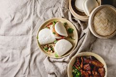 Gua bao buns with pork. Asian sandwich steamed gua bao buns with pork belly, greens and vegetables served in ceramic plate over linen tablecloth. Asian style royalty free stock photo