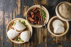 Gua bao buns with pork. Asian sandwich steamed gua bao buns with pork belly, greens and vegetables served in ceramic plate over dark wooden plank background stock photography