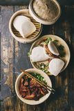 Gua bao buns with pork. Asian sandwich steamed gua bao buns with pork belly, greens and vegetables served in ceramic plate over dark wooden plank background stock photo