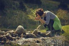 Água bebendo do córrego da montanha da mulher Foto de Stock