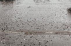 A água de chuva da estrada deixa cair o fundo com reflexão do céu azul e os círculos no asfalto escuro previsão Imagens de Stock