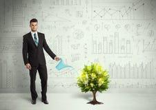 Água de derramamento do homem de negócio na árvore crescente da ampola Fotografia de Stock