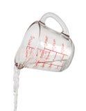 A água derrama o copo de medição Foto de Stock