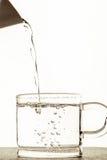 A água derramou em um vidro Fotografia de Stock Royalty Free