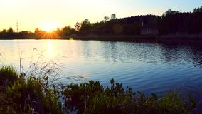 ?gua do lago pequeno que move-se lentamente no por do sol com a casa pequena na costa filme