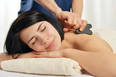 Gua sha acupuncture treatment. Woman receiving gua sha acupuncture treatment on back Royalty Free Stock Photo