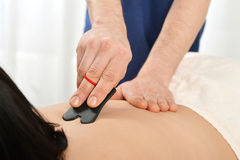 Gua sha acupuncture. Woman receiving gua sha acupuncture treatment on back Stock Image