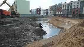 Água Slowmotion da tração do homem com a cubeta da trincheira no terreno de construção vídeos de arquivo