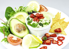 Guacamole. Plate with guacamole in a bowl, decorated with avocado halves, lemon and lime slices, red chili peppers, tomato quarters, salad and nachos Royalty Free Stock Images